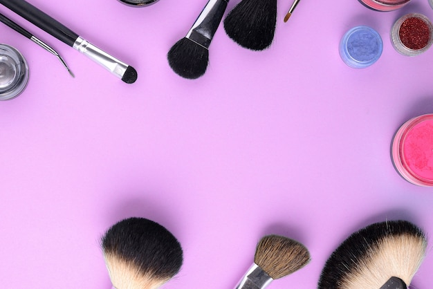 Makeup brushes on a pink background. top view, flat lay, copy space