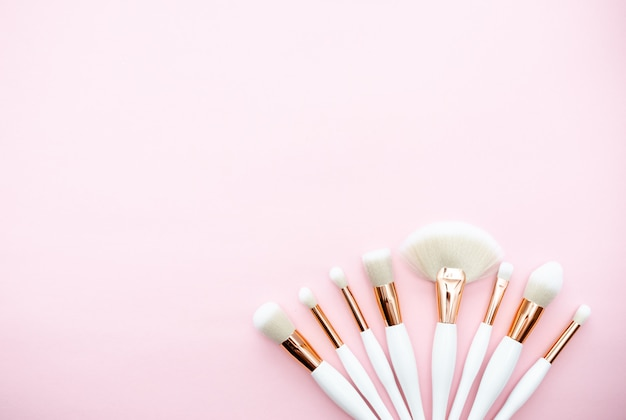 Makeup brushes on a pink background