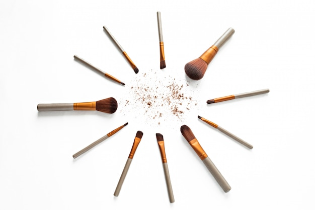 Makeup brushes with crushed cosmetic of professional artist on white