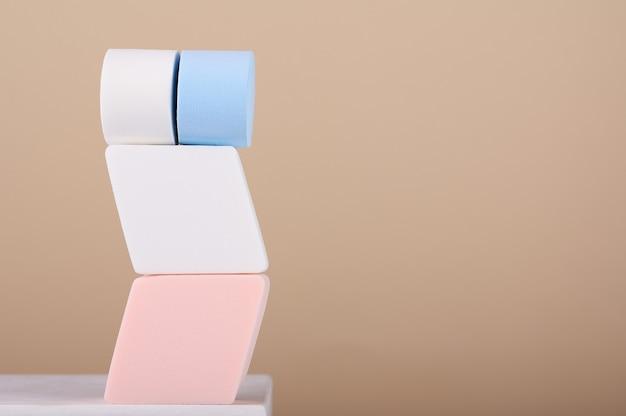 Biege 배경에 흰색 스탠드에 메이크업 다채로운 스폰지. 블렌더 화장품, 파우더, 파운데이션. visagiste를 위한 전문 페이셜 툴. 완벽한 안색을 위한 액세서리. 공간을 복사합니다.