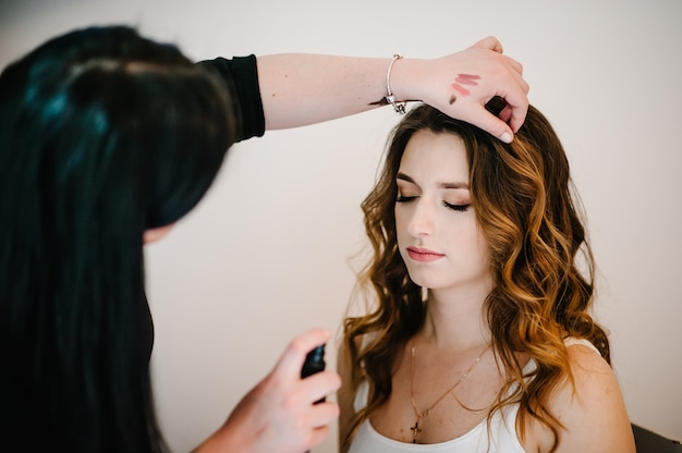 Makeup concept. the makeup artist makes the perfect makeup on the skin face of the model. the stylist spray lacquer on hair beautiful woman. close-up.