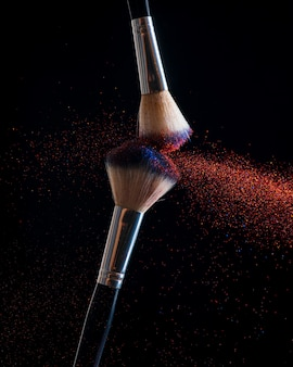 Makeup concept. stop action view of two makeup brushes applying matching red and gold powder