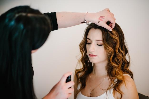 メイクのコンセプト。メイクアップアーティストは、モデルの肌の顔に完璧なメイクをします。髪の美しい女性にスタイリストスプレーラッカー。閉じる。