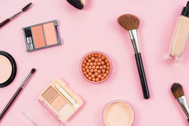 Makeup and cosmetic accessories arrangement on pink background