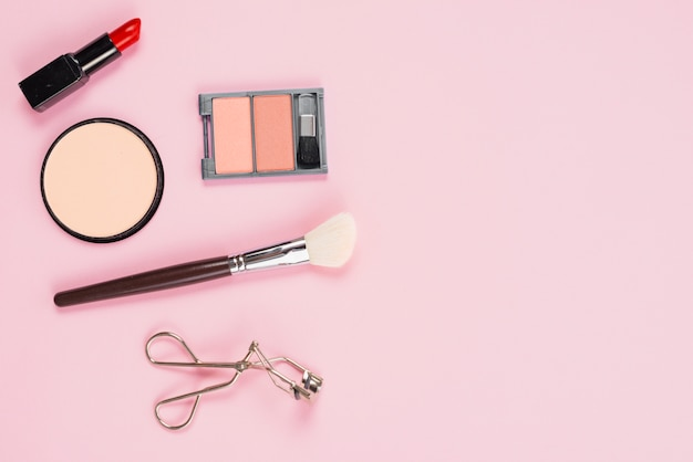 Makeup and cosmetic accessories layout on pink background