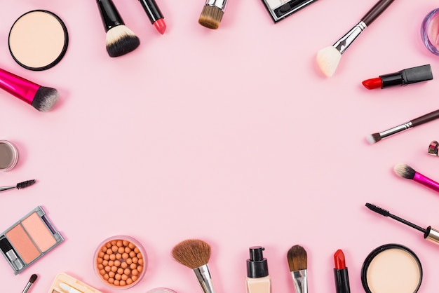 Makeup cosmetics, brushes and other essentials on pink background