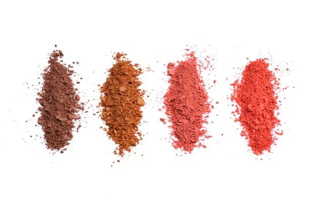 Косметика для макияжа. тени для век коричневого и красного цветов измельченной палитры, красочная пудра теней для век на белом фоне