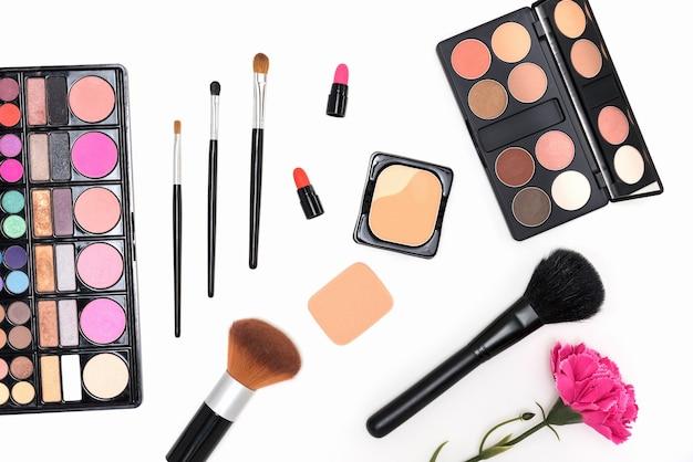 Макияж косметики палитры и кисти на розовом фоне