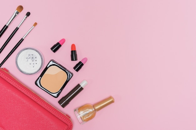 Makeup cosmetics palette and brushes on pink background flat lay