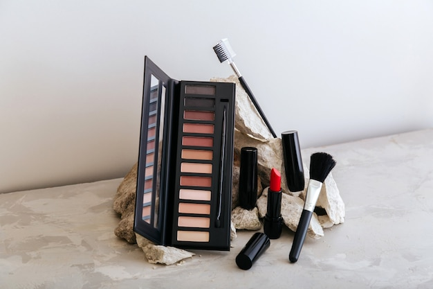 Makeup cosmetics on stone pedestal. red scarlet lipstick eyeshadow makeup brushes on gray concrete background. minimal aesthetic. beauty fashion decorative makeup products.