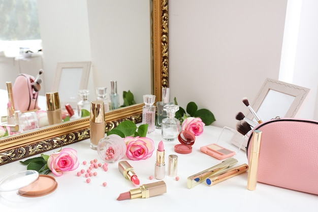Makeup cosmetics with rose flowers on dressing table