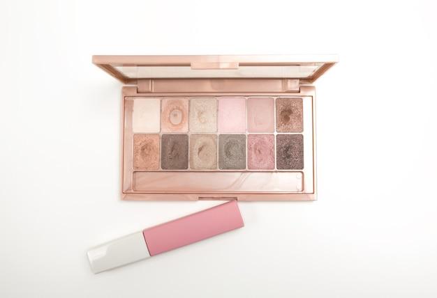 Makeup eyeshadow palette and matt pink liquid lipstick isolated on white background