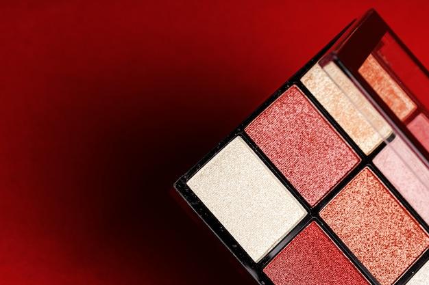 赤の背景に化粧アイシャドウパレット。閉じる。