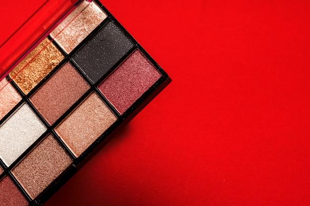 赤の背景に化粧アイシャドウパレット。