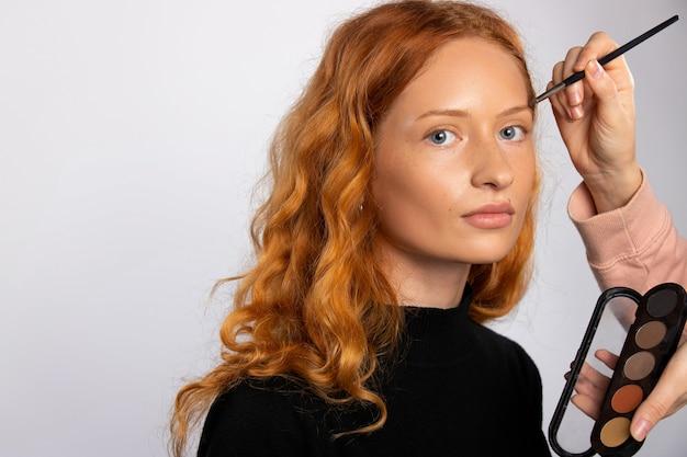赤髪の女性の美容コンセプト化粧ブラシとカラーパレットの白い壁のメイク