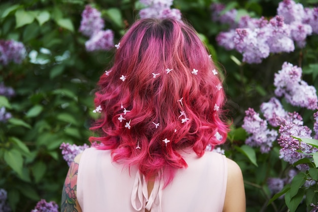 Makeup hair coloring in bright red pink girl hair with lilac flowers. bright saturated color of hair. woman posing in branches lilac