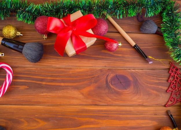 クリスマスの時期の化粧。木の背景に化粧ブラシ。クリスマスプレゼントとしてメイクをする