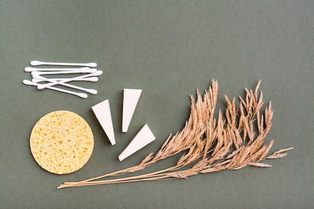 메이크업 아이템. 두 가지 유형의 스폰지, 면봉 및 녹색 배경에 잔디의 귀. 공간 복사