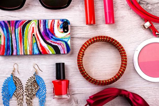 메이크업 키트 및 액세서리. 휴대폰과 선글라스. 멋진 모습을 위한 작은 디테일. 아름다움은 삶의 스타일입니다.