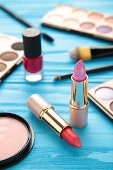 青い背景の上の化粧口紅と化粧品。フラットレイ、上面図。美容とファッションのコンセプト。縦の写真