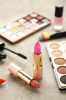 灰色の背景に化粧の口紅と化粧品。フラットレイ、上面図。美容とファッションのコンセプト。縦の写真