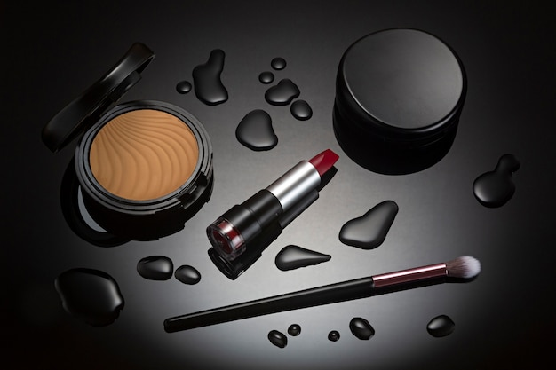 Makeup lipstick and cosmetics on black surface with spot lighting.