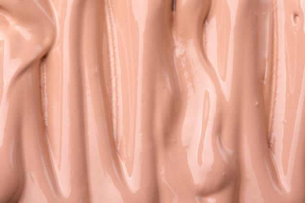 Makeup liquid foundation medium tone smudged blur cream background Premium Photo