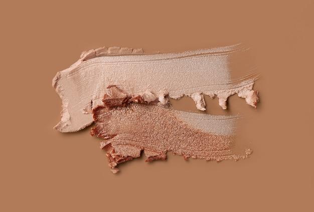 Makeup matte mousse foundation bb cream or concealer smudge creamy powder highlighter on beige background