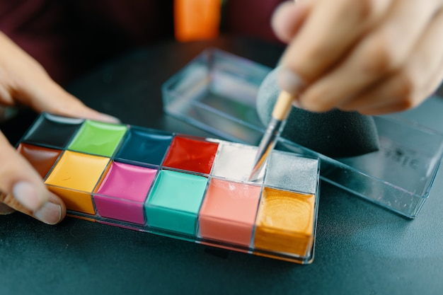 Makeup paints for face painting the process of choosing paints with a makeup brush for coloring prep...