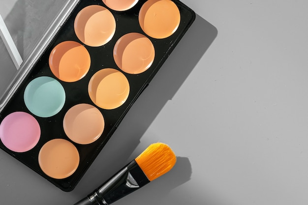 Makeup palette with colorful concealers on gray background