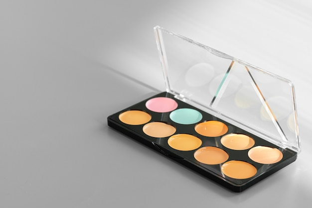 Makeup palette with colorful concealers on gray surface