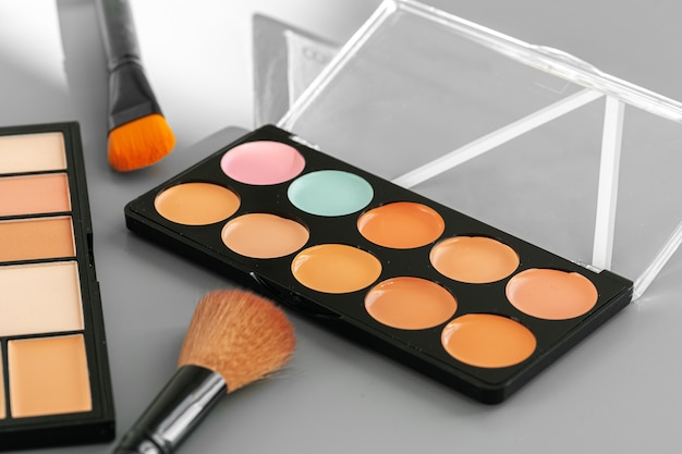 Makeup palette with colorful concealers on gray