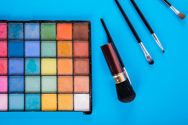 Makeup palettes with various powder colors and brushes on blue background