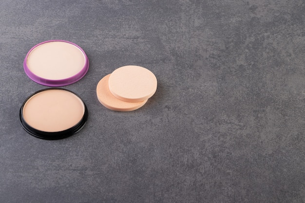 Makeup powder in black round plastic case placed on a stone table .