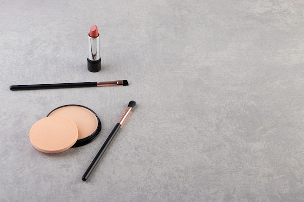 Makeup powder in black round plastic case with lipstick and brushes .