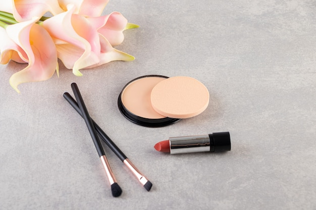 Makeup powder in black round plastic case with palette .