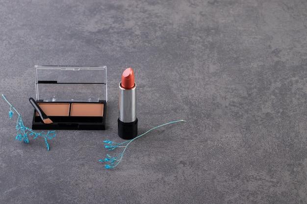 립스틱과 브러쉬가있는 검은 색 원형 플라스틱 케이스의 메이크업 파우더.