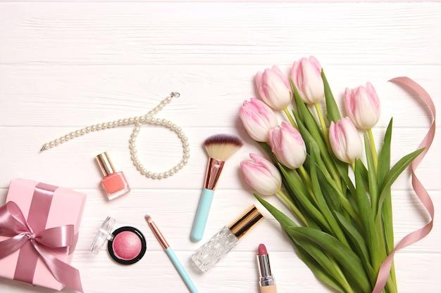 나무 배경 위에 있는 메이크업 제품과 아름다운 봄 꽃