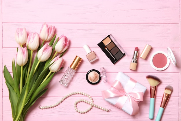 化粧品と木製の背景の上面図の美しい春の花