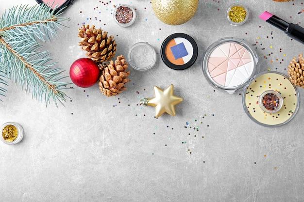 Косметика и рождественские украшения на цветном фоне