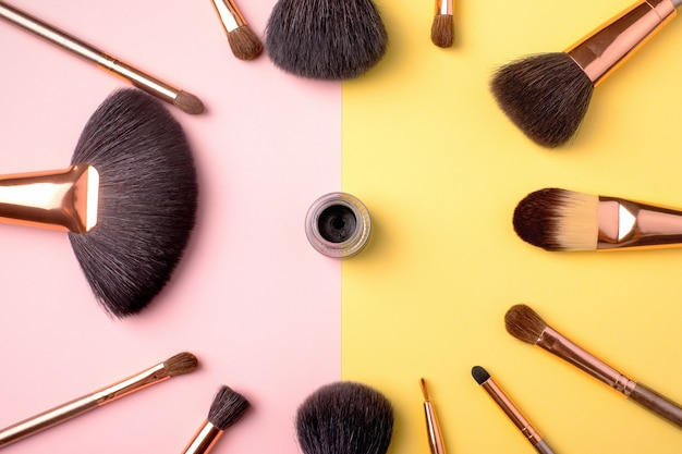 Средства для макияжа и косметические кисти с подводкой на желтый и розовый, плоская укладка.