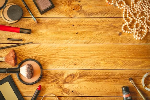 Косметика и украшения на деревянном столе с копией пространства.