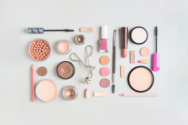 Makeup products arranged in rectangular shape on white backdrop