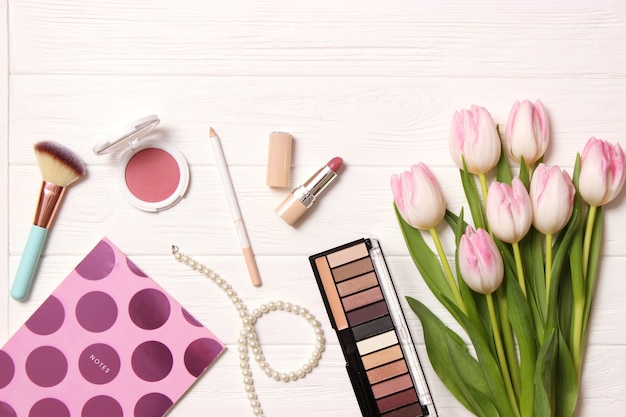 Makeup products and beautiful spring flowers on wooden background top view