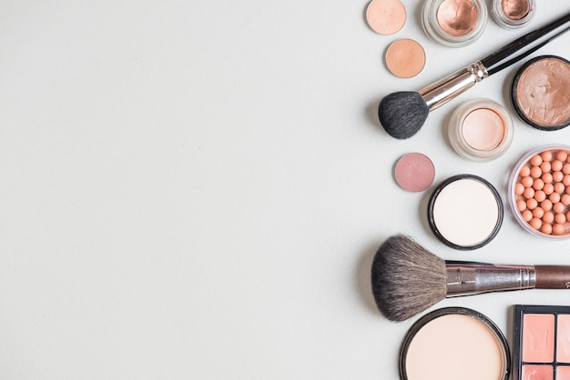Makeup products and brushes on white backdrop
