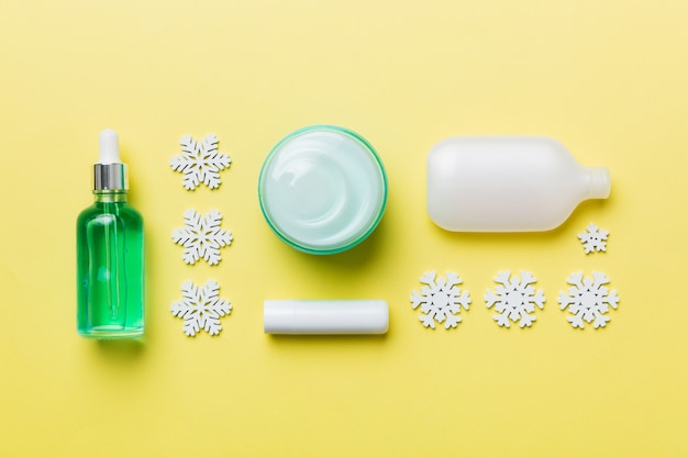 Makeup products and christmas decorations on color background. top view new year beauty concept