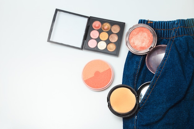 Makeup  products and cosmetic beauty products spilling out from woman denim jeans