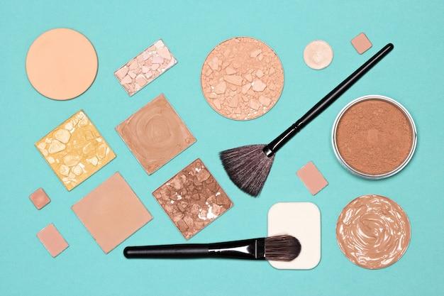 メイクアップ商品フラットレイ。ファンデーション、コンシーラー、メイクアップブラシとスポンジを使った化粧品パウダー