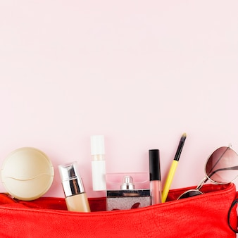 Makeup products lying in red bag