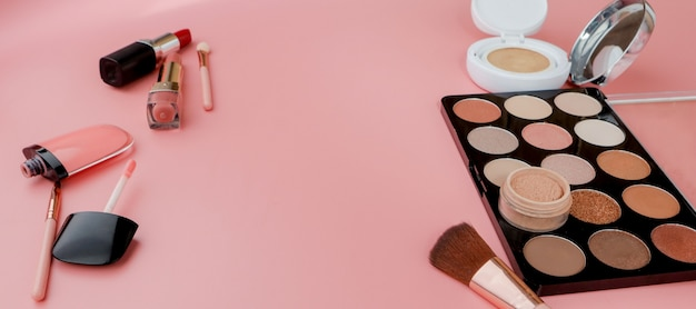 Makeup products on pink background. top view with copy space